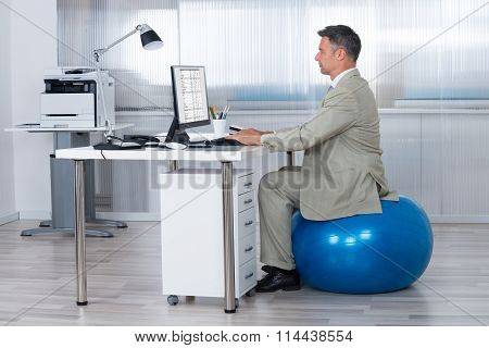 Businessman Using Computer While Sitting On Exercise Ball