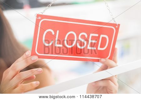 Owner Holding Closed Sign In Clothing Store