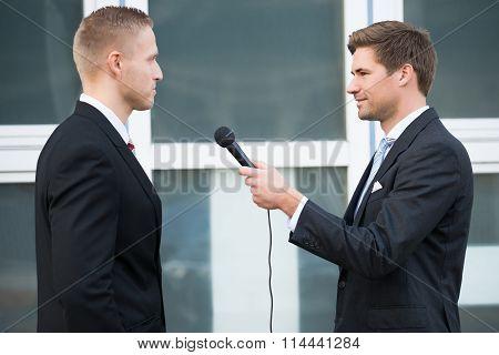 Journalist Interviewing Businessman Outdoors
