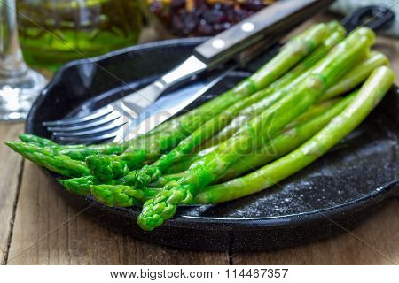 Freshly cooked asparagus appetizer on a cast iron skillet poster