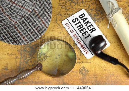 Private Investigation Concept. Sherlock Holmes Deerstalker Cap Sign BAKER STREET Roll Of Paper And Vintage Magnifier On The Old Map Background. Top View.