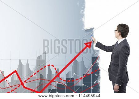 Young businessman painting grey bar charts and red graphs on a white wall with a roller. Side view. Concept of financial calculations. poster
