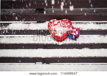 Red Heart Shaped Tin Box And A Gift Box On A Bench