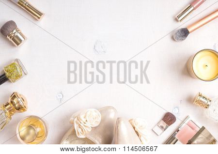 Glamour chic feminine cosmetic background in golden colour. Cosmetic objects frame with gold heels gold glitter nail polish perfume bottle candle blush lip gloss brushes. Getting ready for a party poster