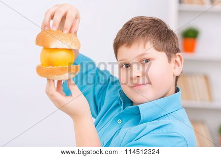 Chubby kid with buns and orange.