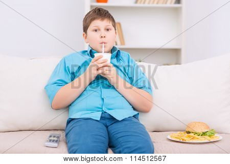 Chubby kid with junk food on the sofa.