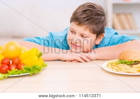 Chubby kid is looking at healthy food plate.