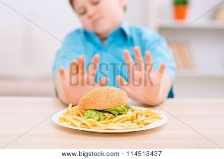 Chubby kid refuses to eat unhealthy food.