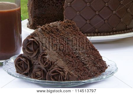 Slice of chocolate cake with whole cake in background cup chocolate milk