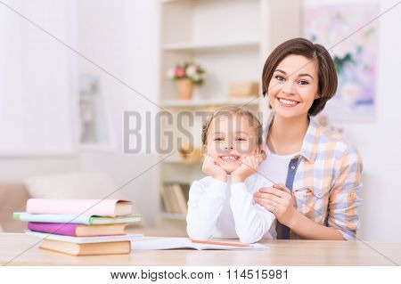 Mom and daughter are both smiling brightly.