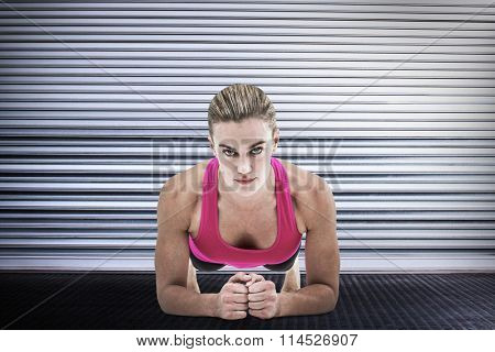 A muscular woman on a plank position against shutter in gym A muscular woman on a plank position on white background