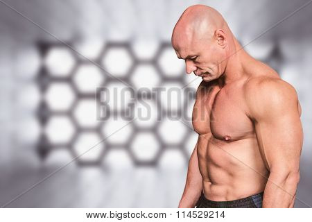 Side view of sad bald man looking down against hexagon room