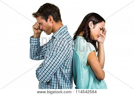 Depressed couple standing back to back against white background