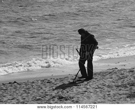 Feodosiya, Russia  - September 28, 2014: man with metal detector on seashore