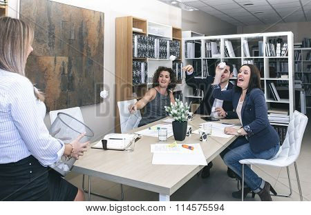 Colleagues throwing papers in basket at office