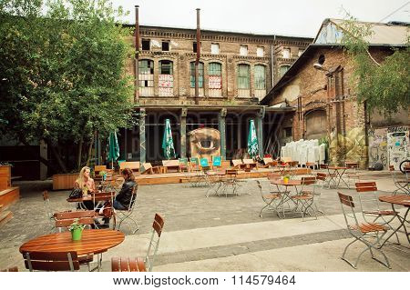 Women Talking At Outdoor Cafe In Grunge Area With Squat And Underground Clubs
