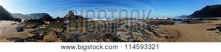 Panorama with exposed lava rock formations at low tide