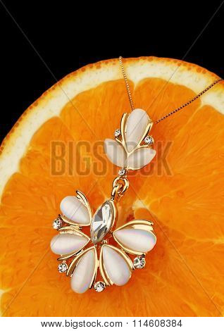 Colourful Golden Jewelry With Nacre And Diamonds On Orange Background