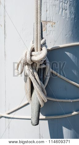 Rope Tied On Cleat Casting Shadow On White Mast