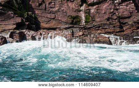 Water Churning And Waves Crashing On Rocky Coast