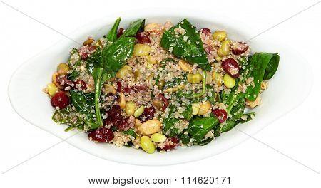 Quinoa Spinach Cranberry Salad in white ceramic bowl. Above top view.