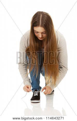 Teen woman tie shoes.
