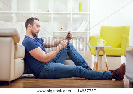 Young Man With Digital Tablet Sitting Near Sofa In Living Room