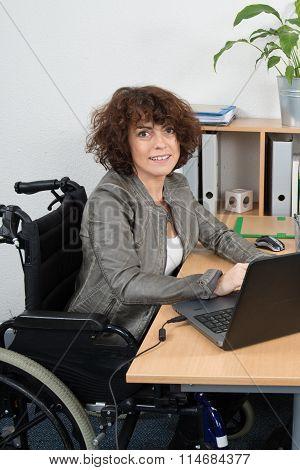 Confident  Businesswoman In Wheelchair Working At Office Desk