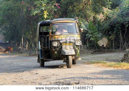 BAIDYAPUR, INDIA - DECEMBER 02: Auto rickshaw taxis on a road in Baidyapur, India, December 02, 2012. Typical mileage for an Indian-made auto rickshaw is around 35 kilometers per liter of petrol.