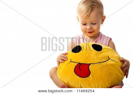 Beautiful baby girl holding a pillow isolated on white poster