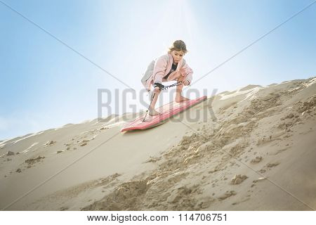 An adventuresome Little Girl boarding down the Sand Dunes