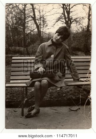 Vintage photo shows a young woman sit on a bench