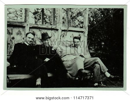 Vintage photo shows people sit on a bench. Photo has green tint
