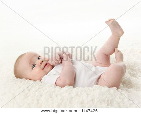 Baby Lying On Back With Feet In The Air And Thumb In Mouth