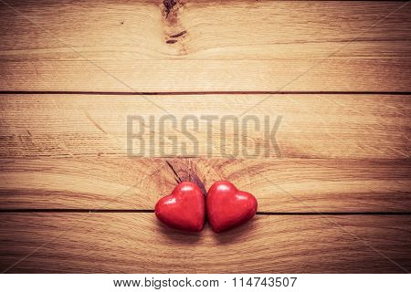 A couple of red little hearts on wood. Vintage concept of love, Valentine's Day. Copyspace for text etc.. Perfect for greeting card.