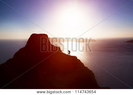 Man climbing up hill to reach the peak of the mountain over ocean. Persistence, determination, strength, reaching the target concepts.