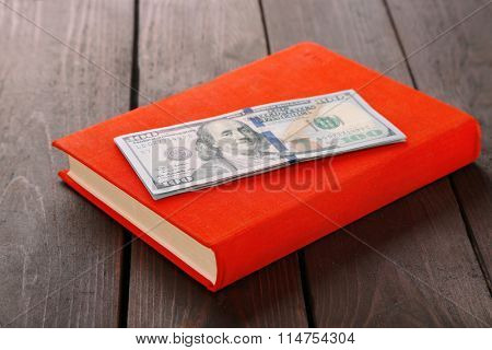 Red book with dollar banknotes on wooden table. Stash of money