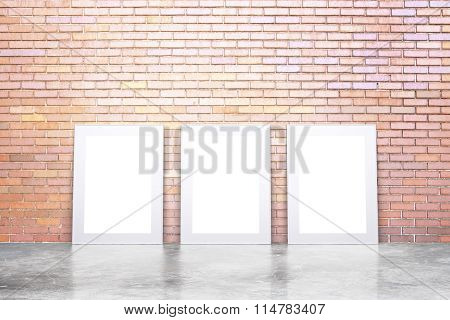 Blank White Picture Frames On Concrete Floor And Red Brick Wall, Mock Up