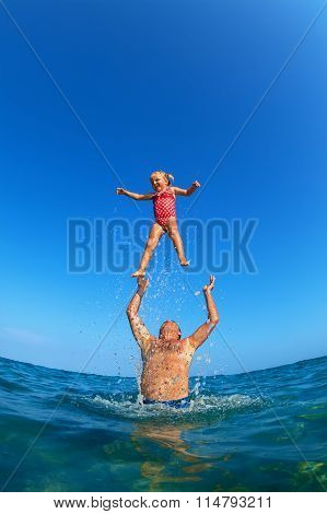 Man Tossing Up Child With Water Splashes In Beach