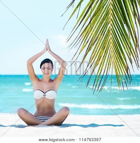 Attractive young lady in sexy swimwear having yoga training on the beach over background with ocean and palm.