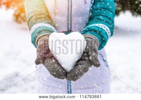 Snow heart in woman's heand. Winter romantic concept