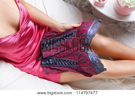 Woman in a sexy corset in the bed