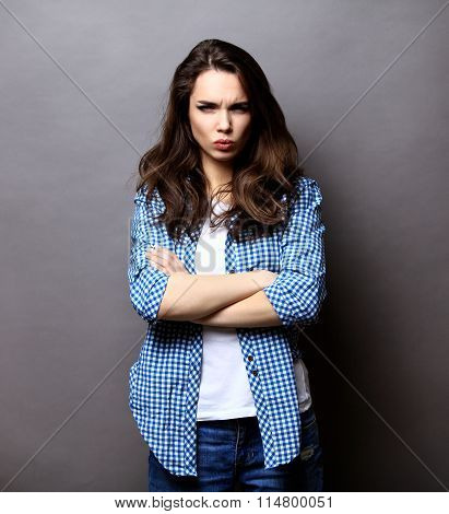 Portrait of angry woman standing with arms folded on gray background