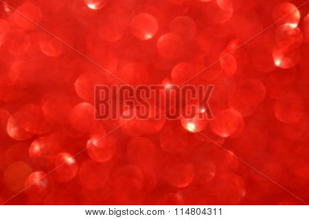 Bright and abstract blurred red background with shimmering glitter