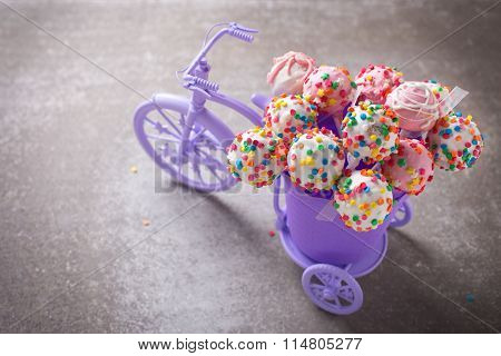 Cake Pops  In Decorative Bicycle On Grey Slate  Background.