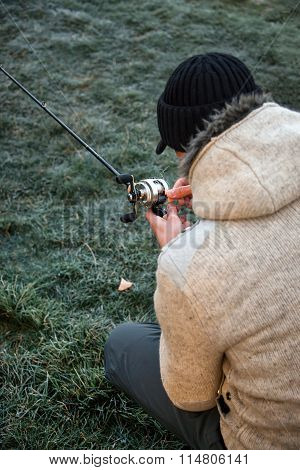 Fisherman sitting on ground and untangle fishing line