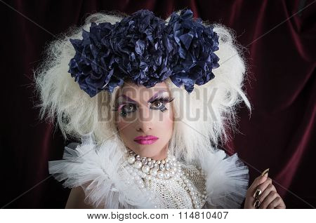 Drag queen with spectacular makeup, glamorous trashy look, posing happily and charming camera