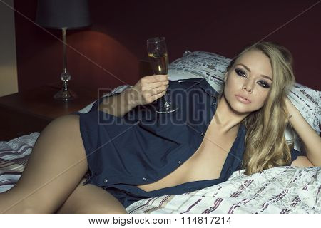 Woman Drinking Champagne On Bed