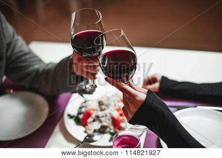 Two People Toasting With Wine Glasses. Young Couple Drinking Red Wine At Bar