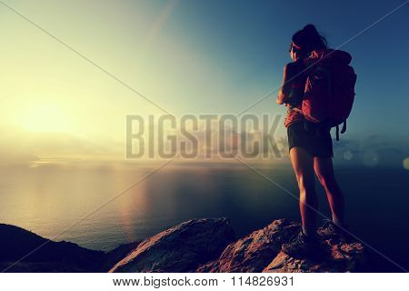 silhouette of young woman hiker hiking at seaside mountain peak